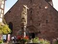 Eglise Sainte-Croix in Kaysersberg, davor der Konstantinbrunnen
