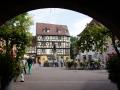 Blick durch die Arakden des Ancienne Douane auf den Schwendi-Brunnen in Colmar